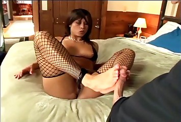 Kinky footjob in ripped up black fishnet stockings