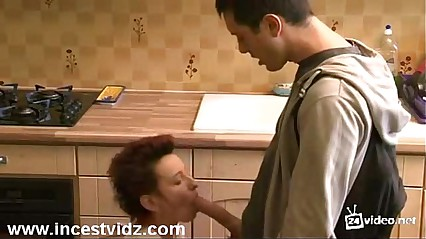 Young boy and mature mom at kitchen
