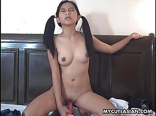 Asian chick stuffs an orange dildo up her tiny cunt succesfully